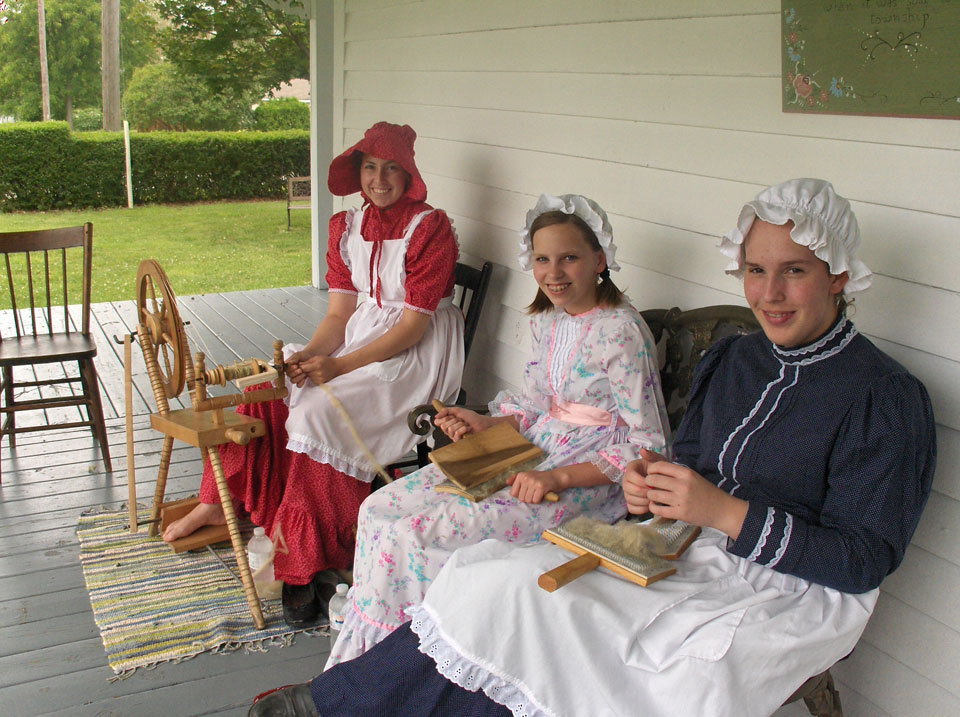 3 girls in pioneer costume carding and spinning wool