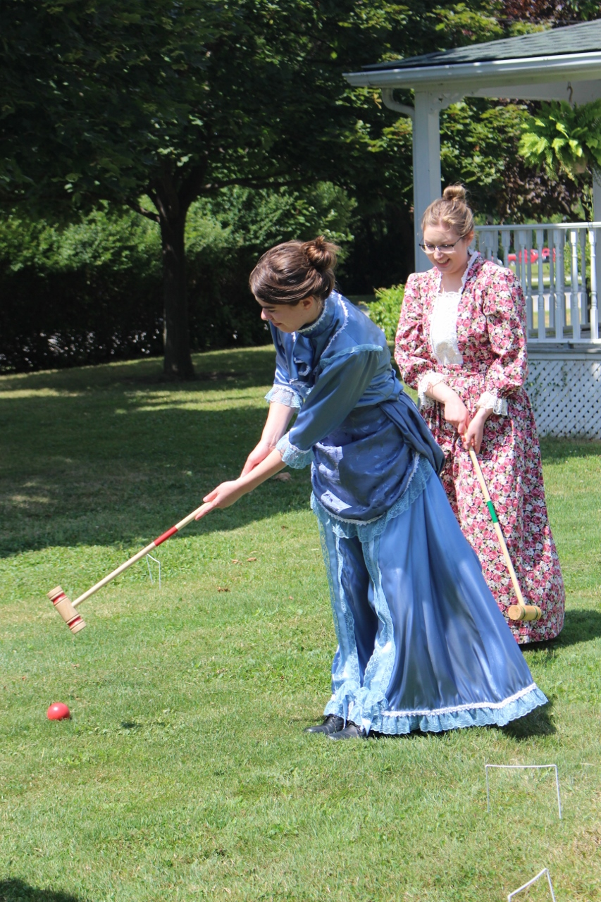 two women in Victorian clothing playing croquet