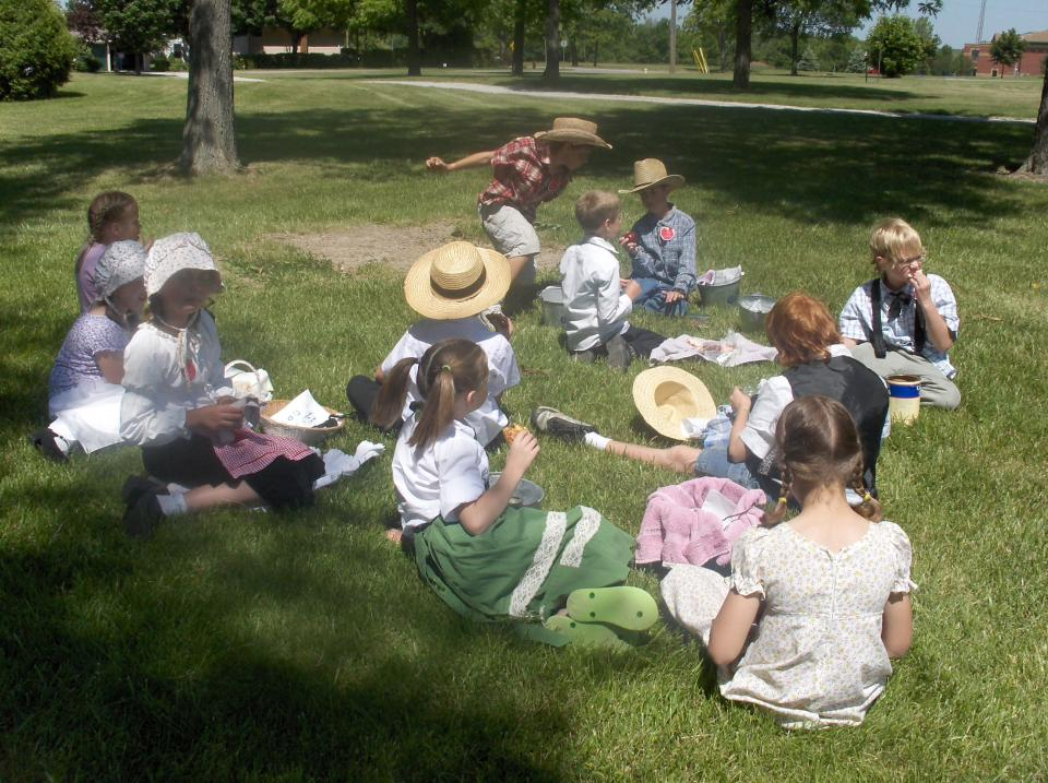 Group of pioneer costumed children gathered on the green grass eating lunch